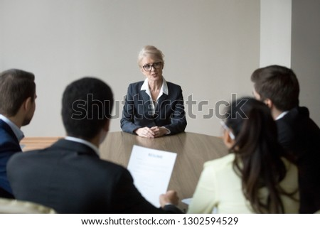 Middle aged senior confident woman applicant seeker talking to young hr managers at job interview making first impression, mature old female candidate speaking answering question, recruiting concept
