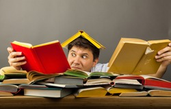 Middle-aged shocked man littered with books, reading, holding two books in hands on a pile of books on table. Concept too much reading. Get lost in the information. A lot of knowledge