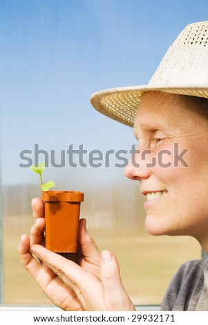 Middle aged smiling woman with sprout in her hands