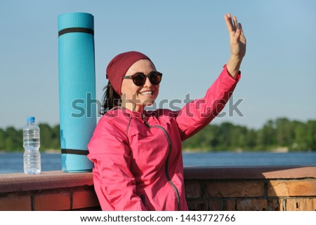 Middle-aged sports woman with yoga mat and bottle of water, an outdoor evening sunny park near the river. Active healthy lifestyle of an age female