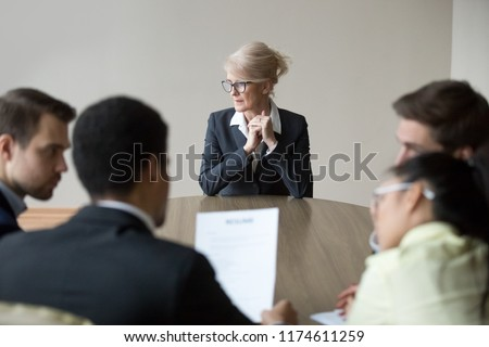 Middle aged stressed woman sitting at the desk in office at meeting. Young multiracial workers team sitting their backs to camera. Passing interview, hiring, recruiting and age discrimination concept