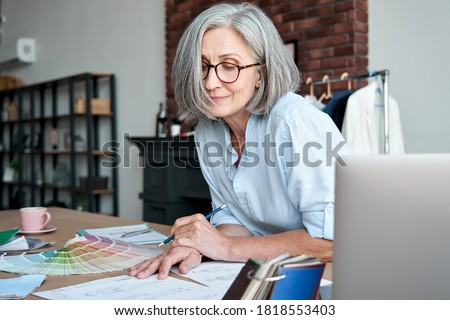Middle aged stylish woman fashion designer drawing sketches in studio office. Mature old adult elegant grey-haired lady dressmaker small business owner creating new fashion design cloth in atelier.