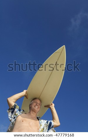 Middle-Aged Surfer Carrying Surfboard