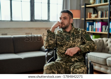 Middle aged thoughtful military man in a wheelchair looking away during therapy session. Disabled soldier suffering from depression, psychological trauma. PTSD concept. Horizontal shot Foto d'archivio ©