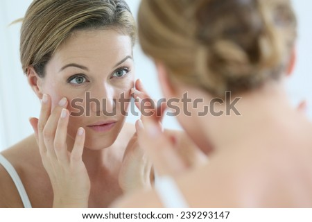 Middle-aged woman applying anti-aging cream #239293147