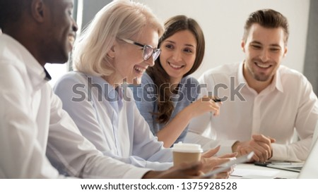 Middle aged woman boss sitting surrounded by millennial diverse colleagues discussing successful work results at boardroom table feels satisfied, collective teammates have fun laughing during briefing