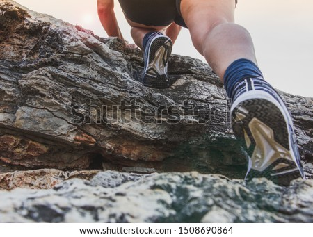 Middle aged woman climbing on the top of a cliff.Closeup legs and feets in sports shoes,  shooting from below.