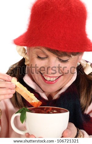 Middle aged woman dipping bread in to tomato soup in winter. - stock photo