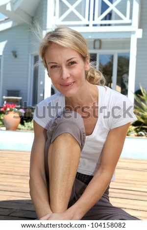 Middle-aged woman doing fitness exercises outside