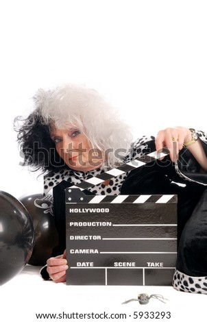 Middle aged woman dressed up as Cruella halloween character, movie clipboards in hand, spiders in foreground