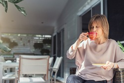 Middle-aged woman drinking coffee or tea enjoying on the balcony.