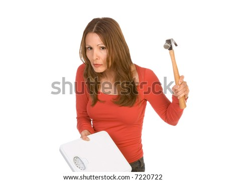 Middle aged Woman hits weight scales by hammer