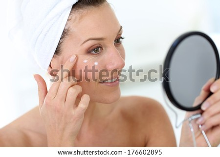 Middle-aged woman in bathroom looking at mirror