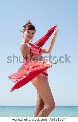 Middle aged woman in red lingerie looks at camera. Woman in underwear at the sea