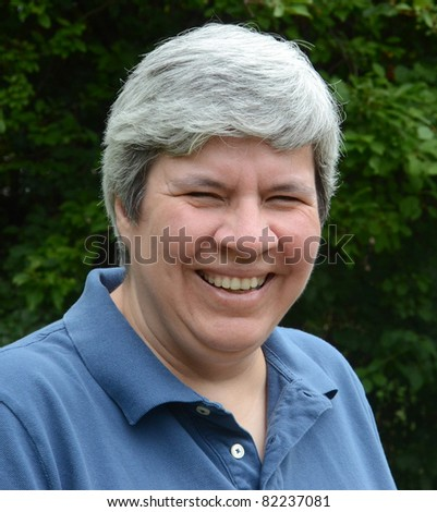 Middle-aged woman laughing with greenery in background - stock photo