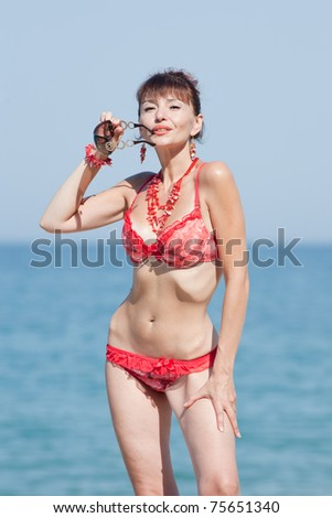 Middle aged woman looking at camera and holds  sunglasses in her hand. Woman at the sea