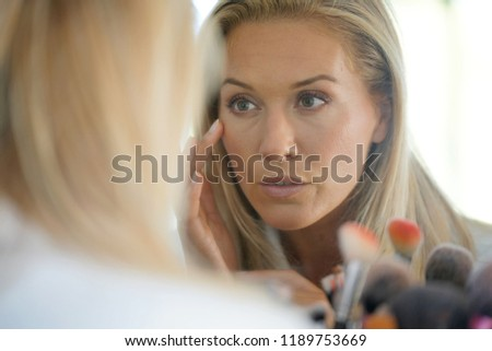 Middle-aged woman looking at her skin in front of mirror #1189753669