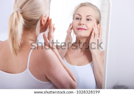 Middle aged woman looking at wrinkles in mirror. Plastic surgery and collagen injections. Makeup. Macro face. Selective focus on the face. Realistic images with their own imperfections. #1028328199