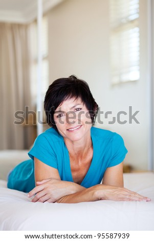 middle aged woman lying on bed relaxing
