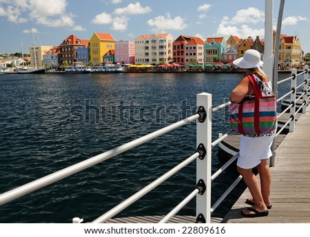 Middle-aged woman on a bridge overlooking a colorful downtown