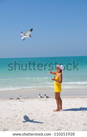 Middle Aged Woman on the Beach Feeding Seagulls
