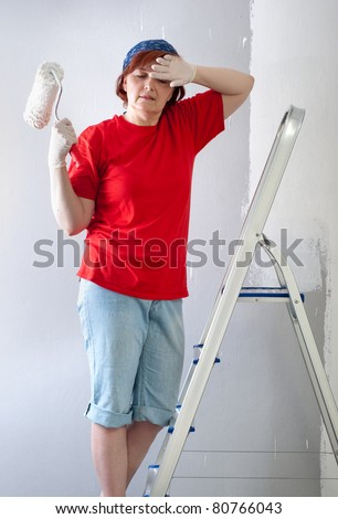 Middle-aged woman painting wall white with paint roller.