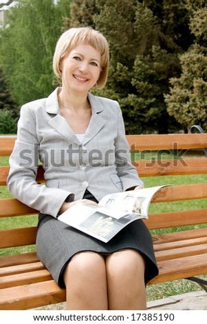 Middle-aged woman reading in a park
