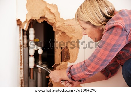 Middle aged woman repairing burst water pipe with a wrench