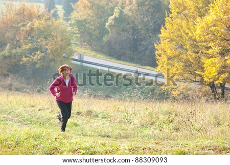 middle-aged woman running through the woods