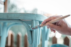Middle-aged woman's hand with brush restores a wooden chair with turquoise paint