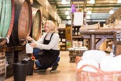 Middle aged woman selling wine on tap from wooden barrels in store, filling plastic can