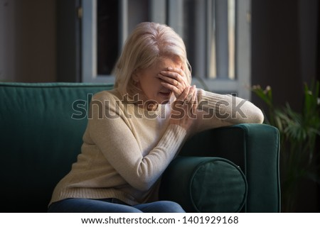 Middle aged woman sit on couch in living room crying covered face with hands received bad news feel desperately, unhappy cheated old female alone at home, divorce break up or oncology disease concept