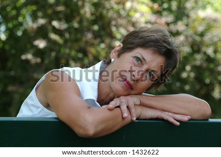 Middle aged woman sitting in a park