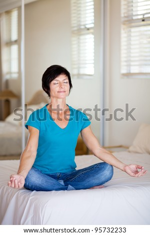 middle aged woman sitting on bed doing yoga meditation