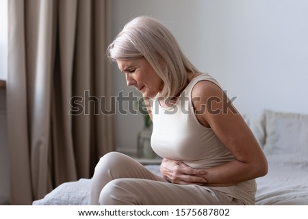 Middle-aged woman sitting on bed feels unhealthy touch stomach suffers from severe crampy abdominal pain, caused by indigestion or diarrhoea, gastric ulcer gastritis problem or unhealthy diet concept