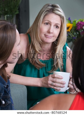 Middle-aged woman smirks while talking with friends