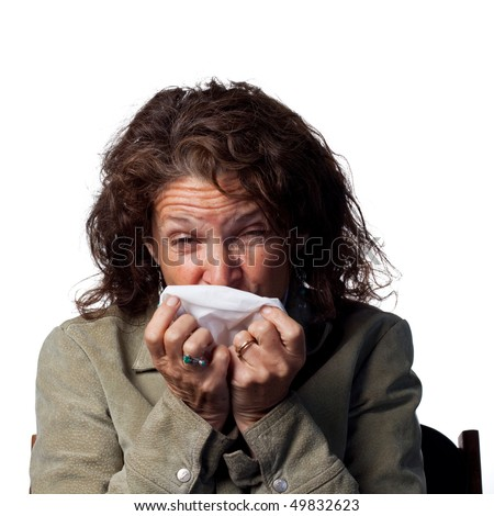 Middle aged woman sneezes into a tissue
