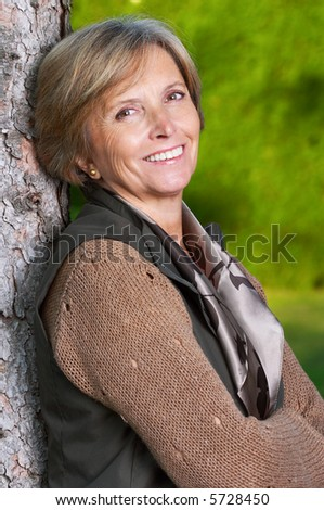 Middle aged woman standing by the tree.