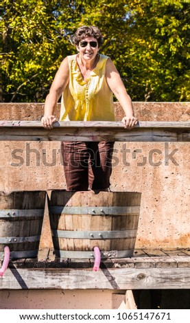 Middle aged woman stomping grapes in a wooden barrel a sunny fall day; Missouri, Midwest