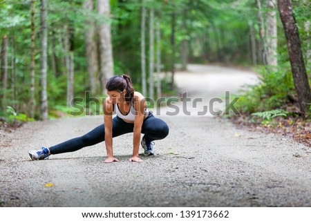 Middle aged woman stretching in the woods on a dirt road before a run