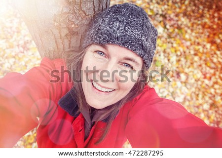 Middle aged woman taking a selfie in the fall