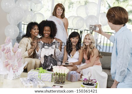 Middle aged woman taking pictures of friends at bridal shower