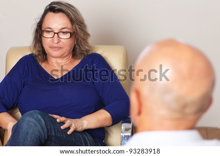 Middle aged woman talking to psychologist - stock photo