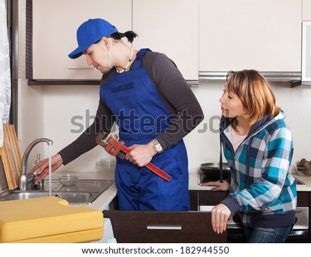 Middle-aged woman watching as worker repairing  water lines