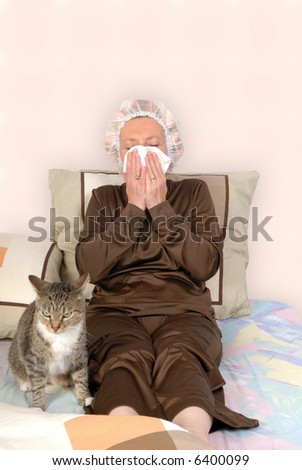 Middle aged woman with cold, sick in bed, blowing her nose.  Curlers and net in hair. Cat keeping her company