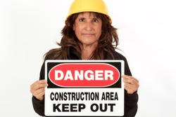 Middle aged woman with long hair wearing a yellow hard hat holding a danger construction area keep out sign isolated on white