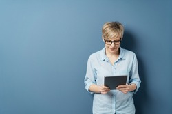 Middle-aged woman with short blond hair in glasses and blue shirt, standing and reading from tablet. Half-length front portrait against plain blue studio background with copy space