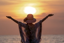 Middle Aged Women Hapy Lift their Arms out while on Sunset  at Beach.