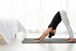 Middle aged women practicing yoga in Downward Facing Dog pose or adho mukha svanasana pose. Working out with yoga in bedroom after wake up in the morning. Concept of exercise, relaxation and he