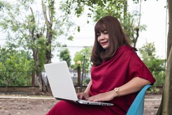 Middle-aged women wearing red red dresses, sitting and working in the park and and working on laptop